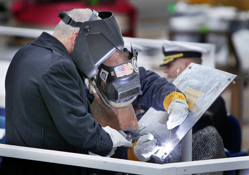 "Welder Carl Pepin is assisted by retired Marine Corps Lt. Col. James G. Zumwalt, left, as Pepin inscribes a steel plate at the keel-laying ceremony. The Zumwalt is named after Adm. Elmo ""Bud"" Zumwalt, a Navy legend whose career culminated in the early 1970s as chief of naval operations. The ship will be christened at another ceremony in 2013."