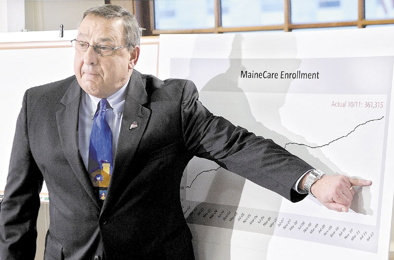 Gov. Paul LePage gestures at graph to show how much lower he'd like to see MaineCare enrollment numbers drop at a news conference Dec. 6 in Augusta.