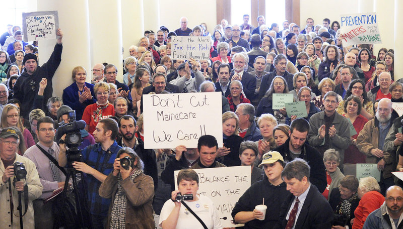 Defenders and opponents of Medicaid cuts fill the State House Hall of Flags on Wednesday in Augusta, where two legislative committees heard testimony on Gov. Paul LePage's proposal to cover a $221 million deficit. The testimony continues today and Friday.