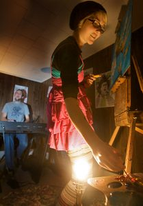 Elizabeth Jancewicz of Pocket Vinyl creates a painting while her husband and partner, Eric Stevenson, sits at the keyboard and sings at a house concert on Jordan Avenue in Brunswick Saturday night. The informal venue, known as The Bombshelter, is booked and operated by resident Nick Dentico. TROY R. BENNETT / THE TIMES RECORS