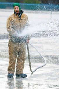 MARK WIESNER of Brunswick Parks and Recreation sprays a steady stream of water on the skating rink at Coffin Pond this morning. Temperatures are expected to stay above freezing for the next few days while dipping into the 20s each night. See forecast on page A12.