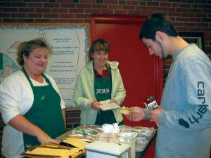THE FOOD SERVICES STAFF at Wiscasset High School have been offering students an opportunity to get some breakfast, a la carte — or more accurately, a la breakfast cart. Food services staff Sherri Faulkingham, left, and Katie wait for senior Corey Hodgdon to make his selection.