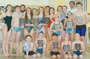 LONG REACH SWIM CLUB members and coaches show off their championship plaques during a Tuesday practice at the Bath Area Family YMCA.