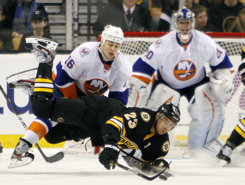 Chris Kelly of the Bruins gets checked to the ice by Marty Reasoner of the Islanders in Saturday's game at Boston. The Islanders won 3-2, ending a five-game road winless streak.