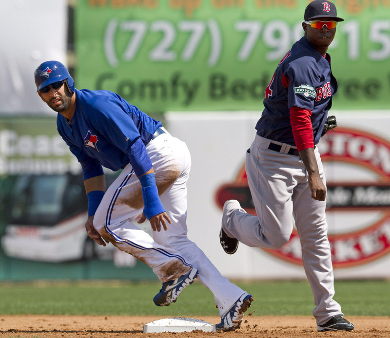 Red Sox second baseman Oscar Tejeda watches his throw to complete a double play as Jose Bautista of the Blue Jays also looks on during Wednesday's game.