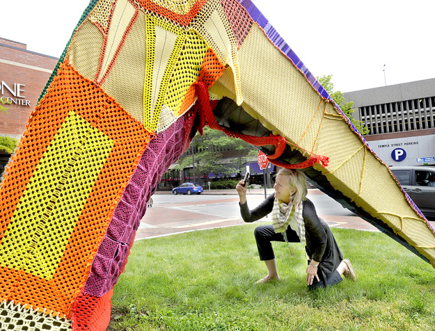 "Jean Barash from Wilson, Wyo., photographs Portland's longtime sculpture ""Michael"" that was partially covered in yarn by people who like to take their knitting to the streets."