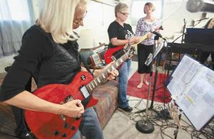 BECCA LINDQUIST, from left, plays guitar with Cheryl Husby and vocalist Diane Winkler during a practice session.