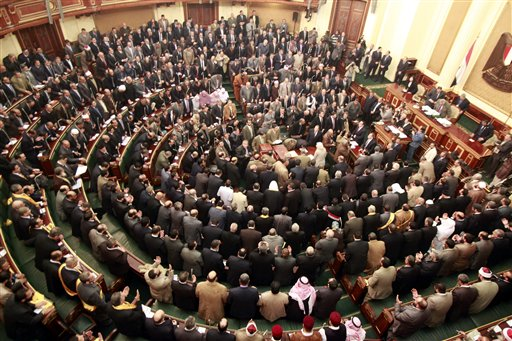 In this Jan. 23, 2012, photo, members of parliament stand and pray for the victims who died during the uprising that ousted President Hosni Mubarak. Egypt's highest court has ordered the country's Islamist-dominated parliament dissolved, saying its election about six months ago was unconstitutional.
