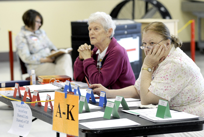Election clerks Christine Thibeault, left, Jane Chesebro and Julia Haigh pass the time at Portland's Ward 1, Precinct 2 polling place at Merrill Auditorium this morning. As of 10 a.m. they had recorded only 30 voters.