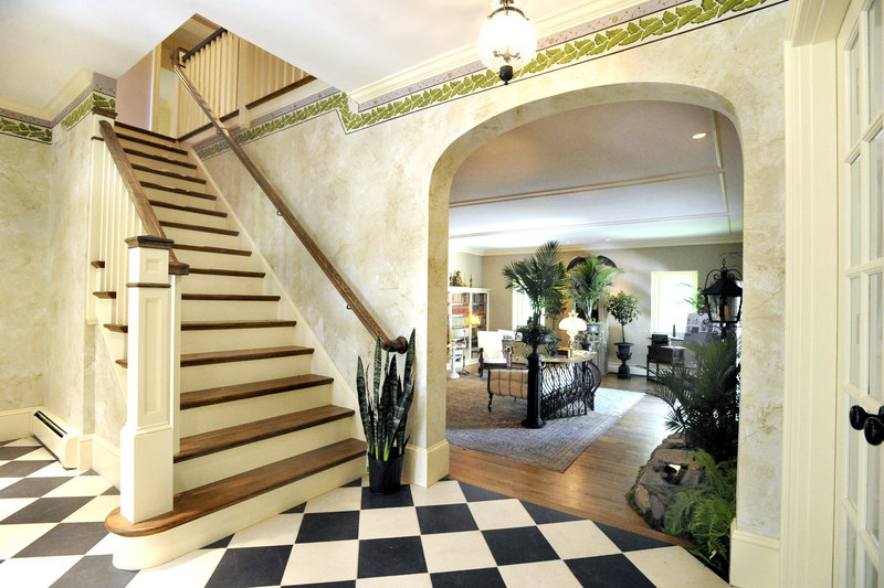 The entrance hall's hand-painted border was inspired by spring in Maine, says designer Lorraine Casinghino of Days Gone By Antiques and Interiors in Royalston, Mass.