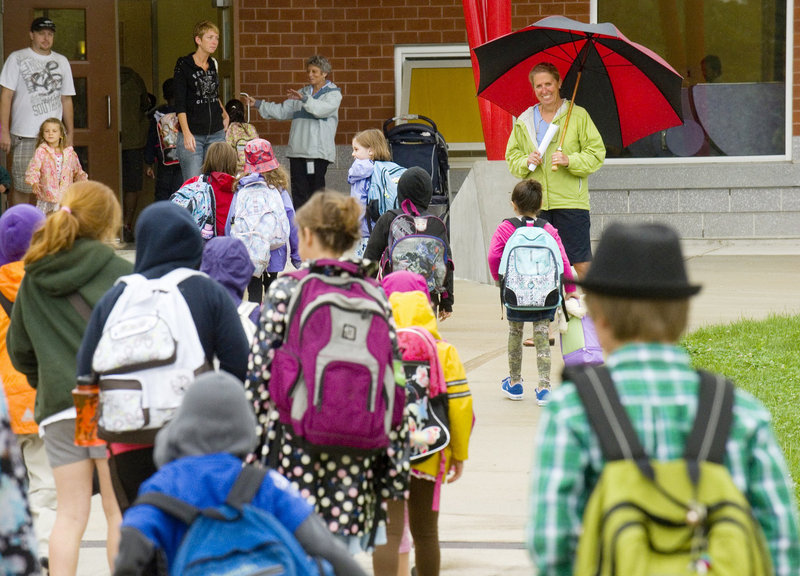 Students arrive at Ocean Avenue Elementary for their first day of school last September, greeted by education technician Jill Marshall. The appeal of a new school apparently prompted many families to move into the Ocean Avenue district in recent months.