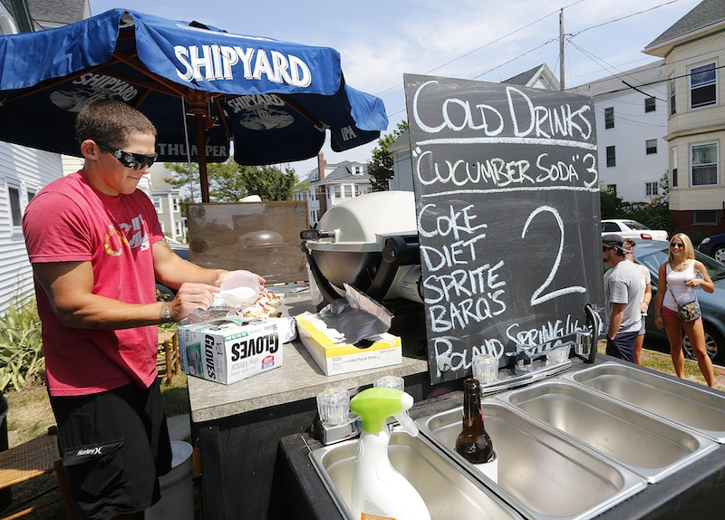 """Eliot Poirier makes some Gyros for customers from his food cart on the corner of Vesper Street and Moody Street on Munjoy Hill in Portland near the """"Gentleman of the Road"""" festival on Saturday."""