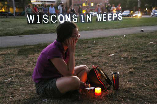 A woman sits with a candle during a vigil for the victims of the Sikh Temple shooting, in Milwaukee on Sunday.
