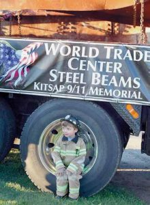 JAYDEN DIETZMAN, 4, of Bremerton, Wash., wears his firefighters outfit as he sits inside the wheel of the semi-trailer carr ying steel beams from the World Trade Center, which came down on Sept. 11, 2001, in New York City. He wants to be a firefighter when he grows up and was resting in the wheel after the 9/11 ceremony was over at Evergreen Rotary Park in Bremerton on Tuesday.