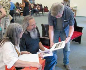 ARTIST Jim McCar thy shares the photograph he is submitting for this year's 10x10 Benefit Art Exhibit and Sale. Fellow artists Lorraine Boucher and Terry Grasse admire. The fifth annual benefit takes place on Friday, Sept. 28, from 5 to 8 p.m. at 23 and 27 Pleasant Street, Brunswick.