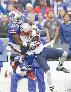 NEW ENGLAND PATRIOTS' Devin McCourty (32) intercepts a pass intended for Buffalo Bills' T. J. Graham (11) during the first half of an NFL football game in Orchard Park, N.Y., on Sunday.