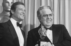 """IN THIS MARCH 29, 1982, file photo, Albert """"Cubby"""" Broccoli, producer of the """"James Bond"""" series, holds the Thalberg Award he received for his work at the Academy Awards in Los Angeles. Roger Moore, left, a British actor who plays secret agent 007 James Bond, made the presentation."""