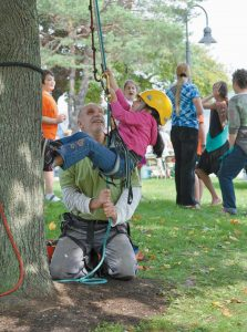 BATH CITY ARBORIST Tom Hoerth teaches Amelia Hoag, 5, the finer art of climbing trees during the annual Autumnfest on Oct. 6. Below, Ken Ladd and his 7-year-old son, Kaiden, build a scarcrow as part of the day's festivities.