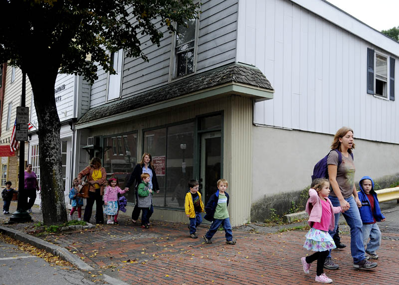 Children walk by 318 Water Street in Gardiner on Wednesday that is available for free for a business to occupy during the months of November and December.