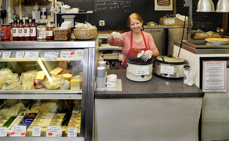 Debbie Sawyer fills a cup with chili at the deli counter at Fresh Approach Market on Brackett Street in Portland.
