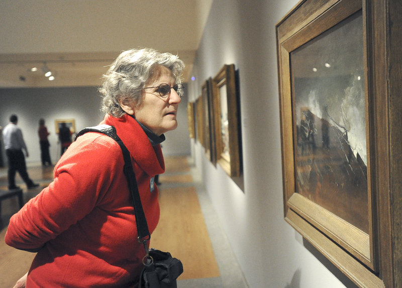 "Jane Rosser of Brattleboro, Vt., on Friday takes a close look at Winslow Homer's 1893 oil painting ""Coast of Maine,"" which is included in the Portland Museum of Art's exhibit titled ""Weatherbeaten: Winslow Homer and Maine."" The museum estimates that 75,000 people will view the show before it closes at the end of the year. Because of its popularity, the exhibition requires advance tickets, and visitation is limited to 60 people each half-hour."
