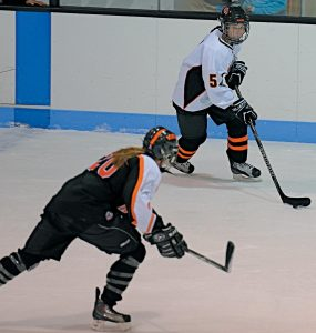 BRUNSWICK FORWARD Rachel Moroney (5, top photo) eyes Winslow's Jennifer Poulin (20) during season-opening girls hockey action at Sidney J. Watson Arena on Friday. Poulin had three goals as the Black Raiders won 4-3. Moroney finished with one goal and two assists. Brunswick defender Maddie Wilkes (12, bottom) tries to track down Winslow's Britany Whitaker.