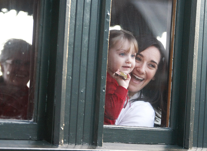 Olivia Magnan, 2, of Auburn, N.H., holds her golden ticket as she waves hello to Santa while riding the Polar Express at the Narrow Gauge Railroad in Portland with her mother, Amy Magnan, on Saturday.