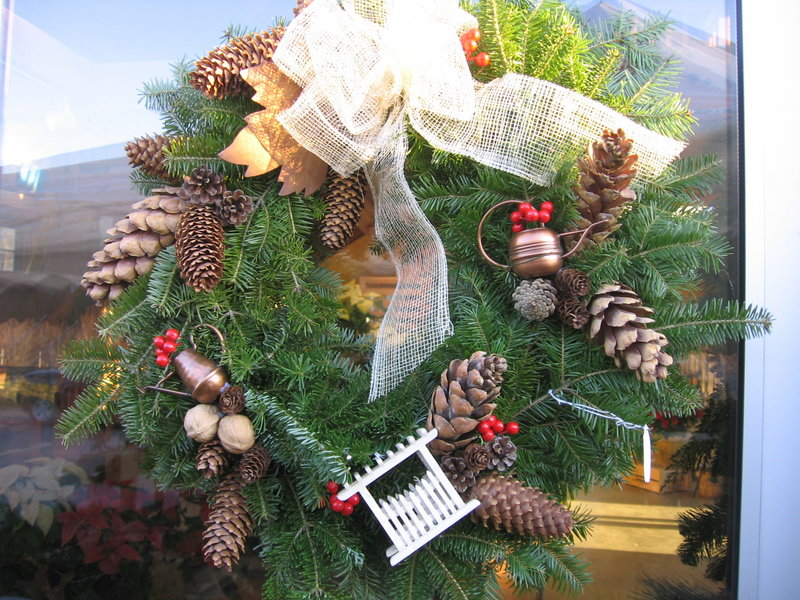 A gardeners' wreath is decorated with mini watering cans, a tiny picket fence, pinecones, berries and a burlap bow. A themed wreath can be a really fresh addition to your holiday decor.