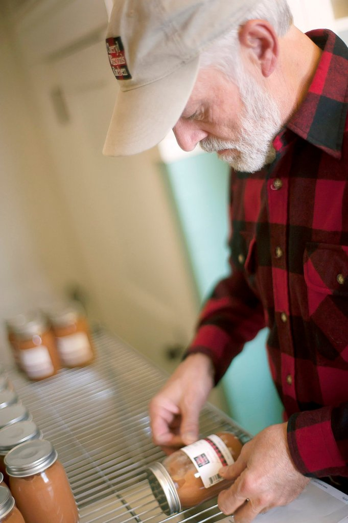 Cheryl Wixson's husband Phil labels jars of applesauce. Last year, he labeled 10,000 jars of Cheryl Wixson's Kitchen foods; this year, the output is 30,000 jars.