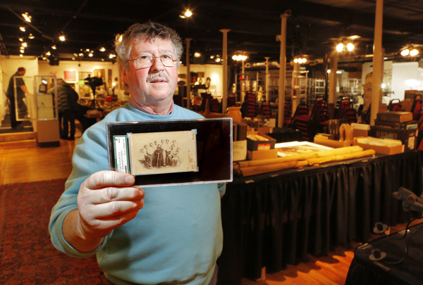 Floyd Hartford, owner of the Saco River Auction Co., holds an 1865 card of the Brooklyn Atlantics baseball team. Only two of the cards are known to exist and the other is at the Library of Congress.
