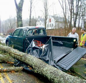 """DANIEL BERGERON of Phippsburg barely escaped what could have been a serious injury this morning when high winds blew a tree down and smashed the bed on the driver's side of his 2009 Toyota Tacoma on Lemont Street in Bath. Lt. Stanley Cielinski said that Bergeron had moved just to the right to avoid a smaller limb moments earlier. """"If he had stayed where he was, he probably would have been hit — a very lucky man,"""" Cielinski said. Bergeron, left, talks with Tom Ramsey of Bath Public Works."""