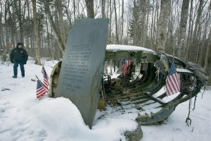 GREENVILLE POLICE CHIEF JEFF POMERLEAU views a monument next to wreckage from a B-52 bomber on Elephant Mountain last month. The plane's 40-foot-tall vertical stabilizer had snapped off and crashed on Jan. 24, 1963. Seven of the nine people on board died in the crash.