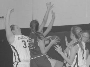 RICHMOND'S ALYSSA PEARSON (33, top photo) blocks the way for Rangeley's Emina Gunic (31) during an East-West Conference high school girls basketball game on Tuesday in Richmond, while in the bottom photo, Bobcats forward Jamie Plummer goes inside against Rangeley players Blayke Morin (20), Seve Deery-Deraps (11), Abby Abbott (12) and Tori Letarte (14). Even though Plummer didn't score on this play, the senior had 25 points in Richmond's 50-37 victory.