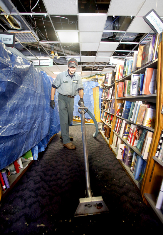 Dustin Souza vacuums up the water from the carpet at Longfellow Books in Portland on Sunday.