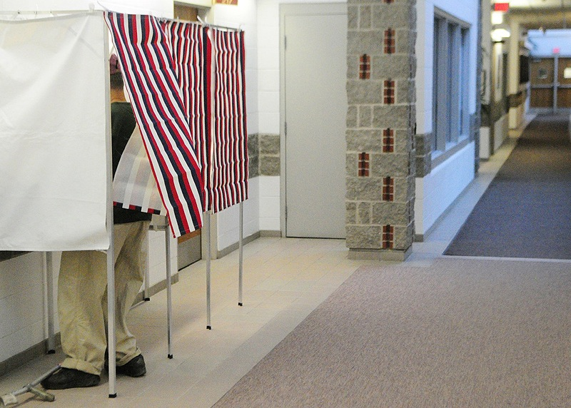 A voter fills out an absentee ballot in a voting booth in the hallway near the Augusta city clerk's office.