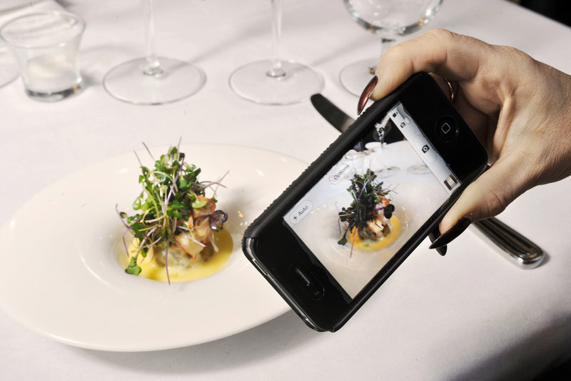 A diner uses her iPhone to photograph a serving of butter-poached lobster risotto at David's Opus Ten in Portland's Monument Square.