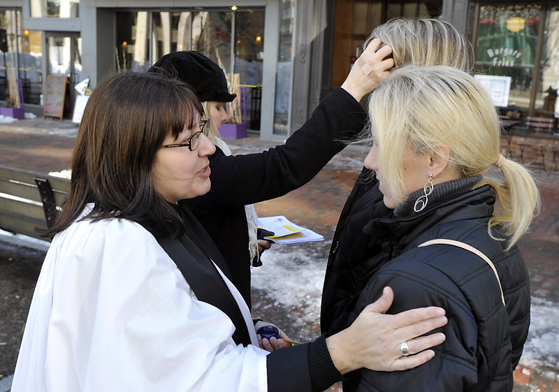 Nina Pooley, left, talks with Kristine Taylor of Portland after putting the ashes on her forehead as Gwen DeCicco, left rear, puts ashes on the forehead of Suzanne Parent of Portland.
