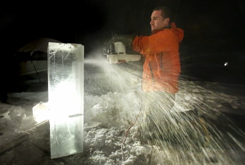 Gregory Rec/Staff Photographer: Ice sculptor Jesse Bouchard uses an electric chainsaw to cut out a detail area on a block of ice at his South Portland home on Tuesday, February 12, 2013. The blocks will be constructed into an ice bar at the Hilton Garden Inn in Freeport on Friday night.