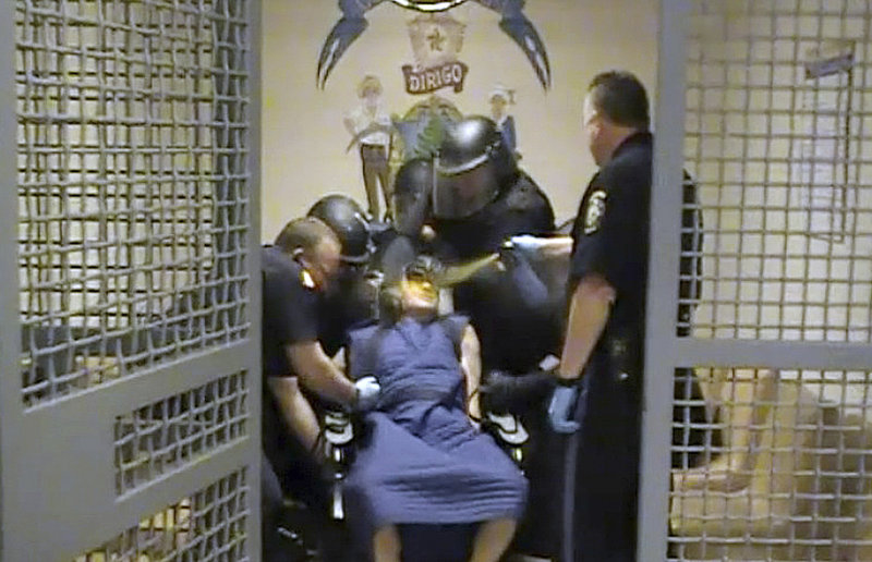 Capt. Shawn Welch sprays pepper spray into the face of Maine Correctional Center inmate Paul Schlosser, who is bound in a restraint chair, June 10, 2012. Welch told an investigator that the use of pepper spray was appropriate because Schlosser, who has hepatitis C, had spit at an officer.