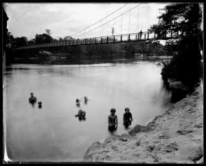 """""""SWIMMERS AND SWINGING BRIDGE, Topsham, Androscoggin River, Maine, 2012"""" is a unique ambrotype that's part of Brunswick photographer Michael Kolster's photographic work documenting the rise and fall of American rivers, including the Androscoggin River. Kolster was selected as a 2013 Guggenheim Fellow for his work."""