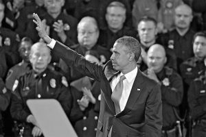 DENVER POLICE applaud as President Barack Obama waves after speaking at the Denver Police Academy on Wednesday. Obama also met with local law enforcement officials and community leaders to discuss the state's new measures to reduce gun violence.