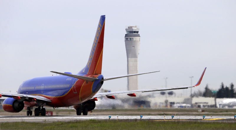 A Southwest airlines jet waits to depart in view of the air traffic control tower at Seattle-Tacoma International Airport in Seattle on Tuesday.