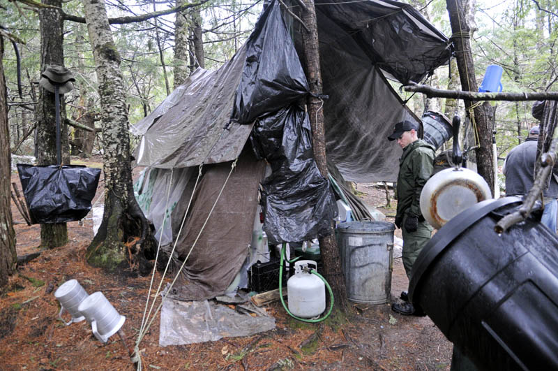 District Game Warden Aaron Cross inspects Christopher Knight's camp Tuesday.