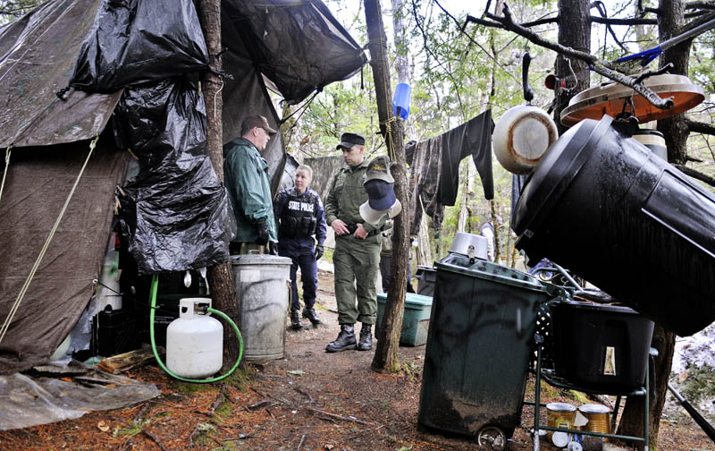 Game Warden Sgt. Terry Hughes, right, Maine State Police Trooper Diane Perkins-Vance, center, and Somerset County Deputy Sheriff Jeremy Leal on Tuesday inspect Christopher Knight's camp in a remote, wooded section of Rome.