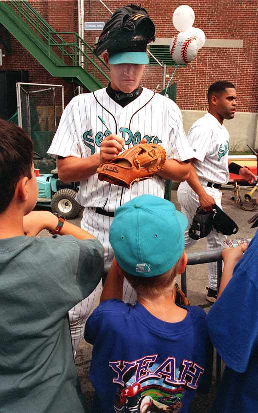 STAFF PHOTO BY DAVID MACDONALD - Monday, September 7, 1998 - Sea Dogs pitcher Mark Richards balances his baseball glove on top of his head while signing sutographs for young fans shortly before the start of the Sea Dogs last game of the season at Hadlock Field.