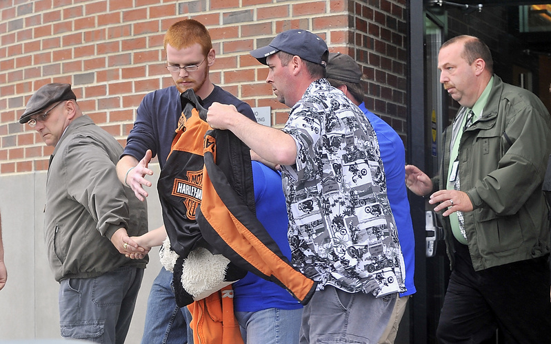 Nichole Cable's mother is being shielded by a coat as her family leaves Penobscot County Superior Court in Bangor on Wednesday after Kyle Dube's arraignment on a charge of murdering Nichole.