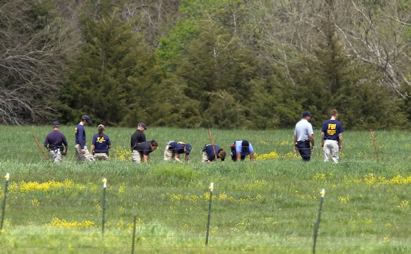 Law enforcement officials scan the fields behind a farm Thursday, May 9, 2013 in search of an 18-month-old baby in rural Ottawa, Kan., where three bodies were found on Monday. Authorities in eastern Kansas said Thursday they have arrested a 27-year-old suspect in the deaths of three people whose bodies were found at a farm, and that a fourth victim — an 18-month-old girl — was found Sunday, May 12, 2013. (AP Photo/The Topeka Capital Journal, Chris Neal)