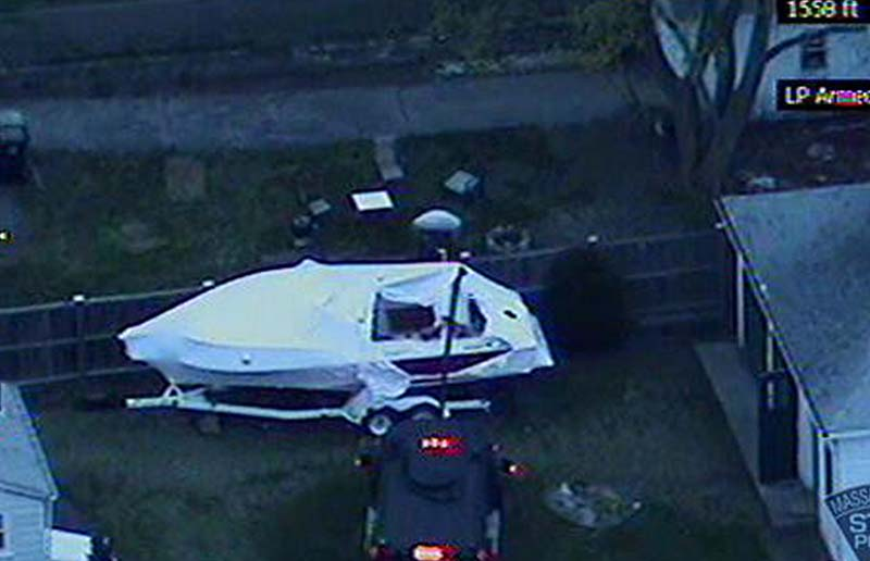 This image made available by the Massachusetts State Police shows a police vehicle probing the boat where 19-year-old Boston Marathon bombing suspect, Dzhokhar Tsarnaev, was hiding in Watertown, Mass. He was pulled, wounded and bloody, from the boat parked in the backyard of a home in the Greater Boston area.