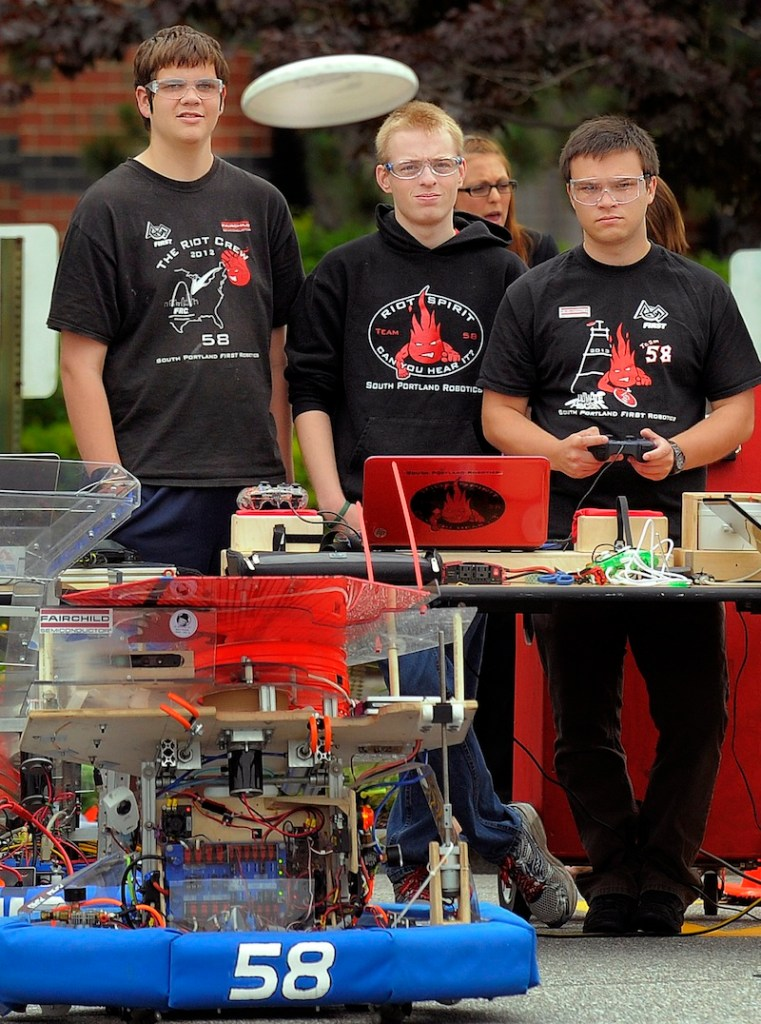 Members of the South Portland Robotics team, left to right, Alex Manning, Ross Usinge and Aaron Davies, watch as a Frisbee flies out of their robot at Fairchild Semiconductor in South Portland on Thursday. Gov. Paul LePage and inventor Dean Kamen were on hand.