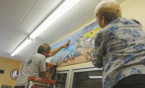 WAYNE BARTLETT, left, and Anne Magalis hang the final piece of a mural that Magalis spent several weeks creating for the Lighthouse Variety and Deli on Harpswell Road in Brunswick. The artwork went up Monday, and Bartlett and his business partner, Becky Marcos, plan to reopen the storefront on Thursday. Five panels of acrylic on pressboard, the mural is an evolutionary depiction of Maine's labor industry from farming and logging, to building and fisheries, and finally to tourism and retail. It's a home-grown version of the mural that Gov. Paul LePage had removed from the Department of Labor in 2011, Marcos said.